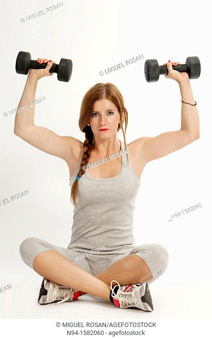 Young woman, redhead, sitting, exercising with weights at the gym