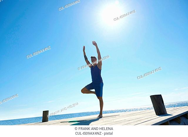 Man on pier standing on one leg arms raised exercising