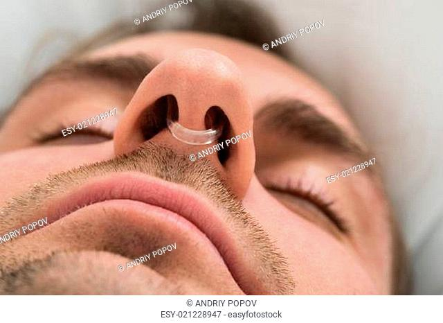 Extreme Close-up Of Man Face With Nose Clip Device