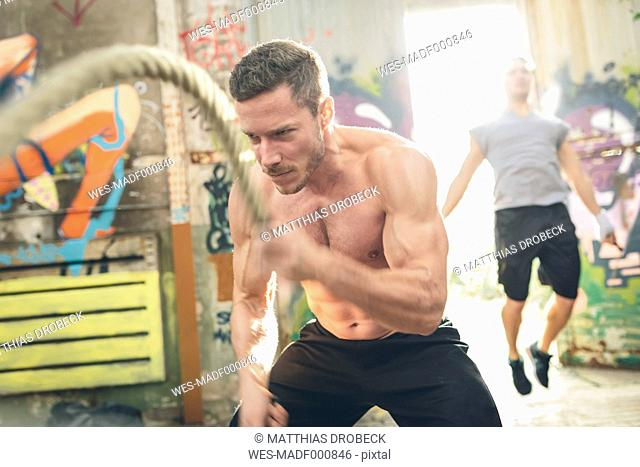 Young man having a workout with ropes