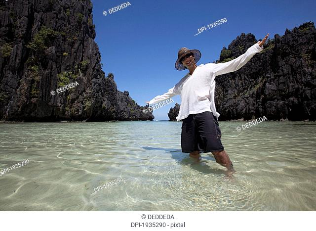 man standing in clear water of small lagoon, miniloc island, palawan, philippines