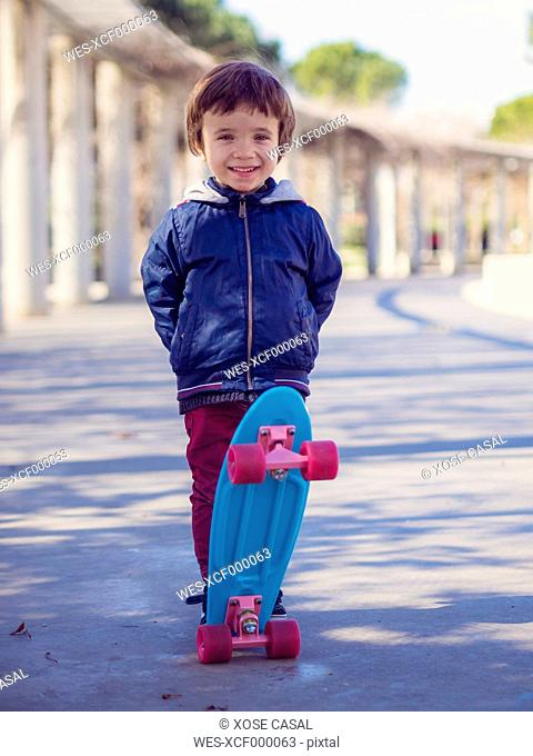 Portrait of smiling little boy with skateboard