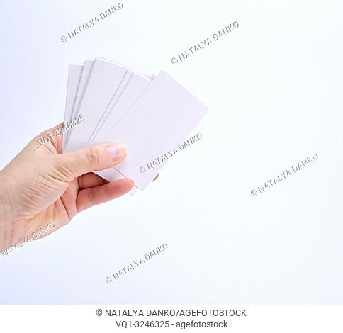 stack of empty white paper business cards in a female hand on a white background