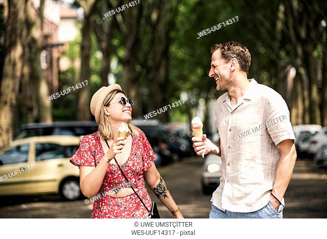 Happy couple with ice cream cones walking in the city