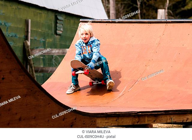 Boy preparing to sit down on skateboard on wooden skateboard ramp