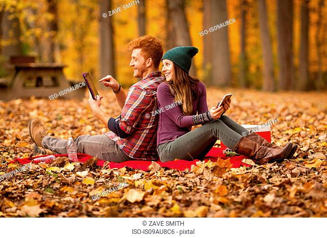 Young couple back to back using digital tablet and smartphone in forest