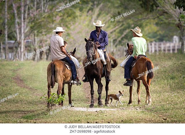 Cowboys on horseback near Hacienda La Belen, Cuba, stop on the trail to talk