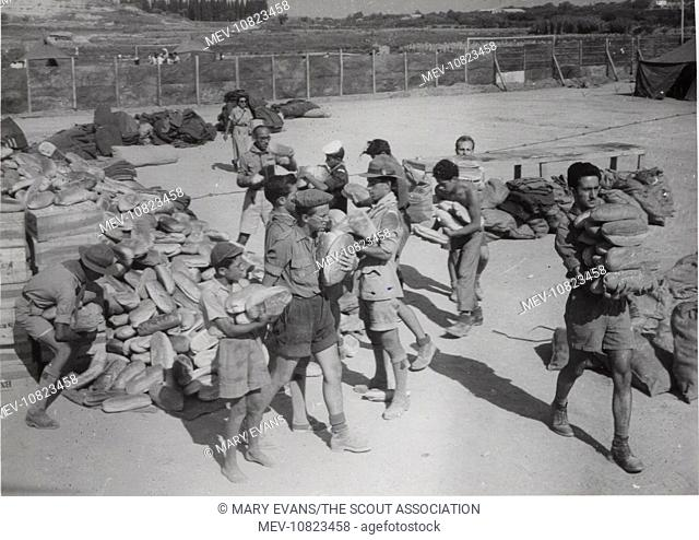 Scouts distributing bread in Argostolion, Kefalonia, Greece. Four earthquakes hit the island in August 1953, destroying many buildings; the scouts helped with...