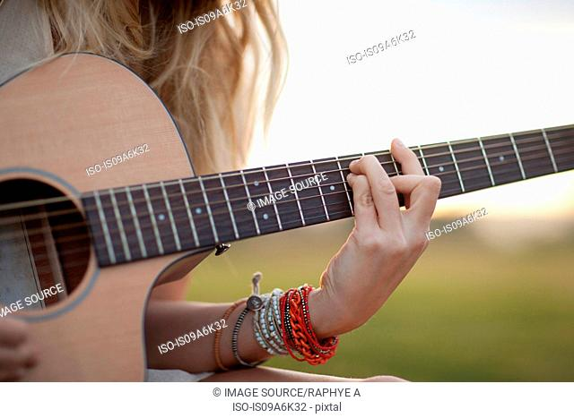 Woman playing guitar in grass