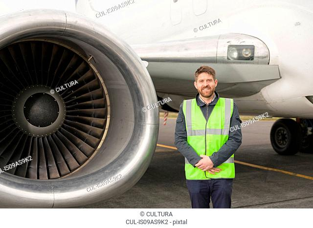 Mid adult man wearing high visability jacket standing next to airplane engine, hands together, looking at camera smiling
