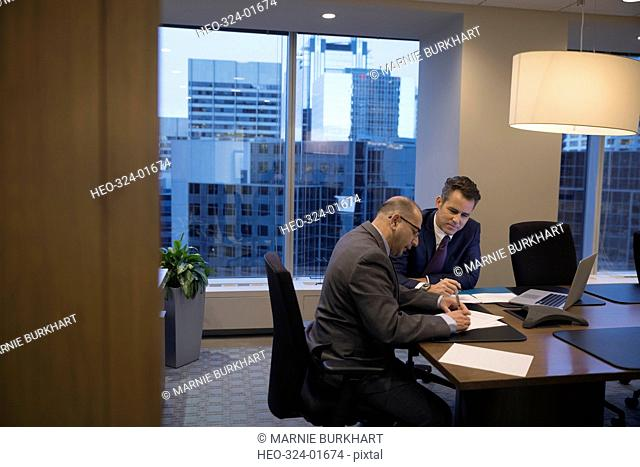 Male lawyers reviewing and signing contract in conference room meeting