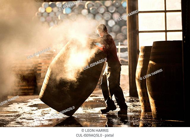 Male cooper working in cooperage with whisky casks