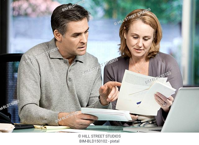 Caucasian couple paying bills online together