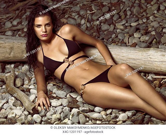 Beautiful young woman in black bikini posing on a pebbled beach  High fashion photo