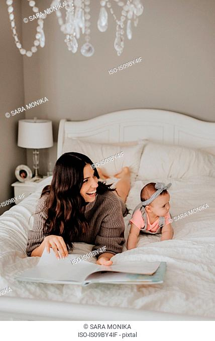 Mother reading with baby daughter on bed in bedroom
