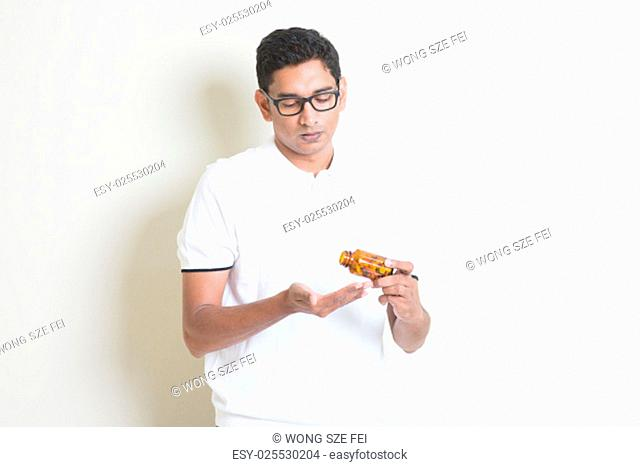 Sick Indian guy taking tablet medicine. Asian man standing on plain background with shadow and copy space