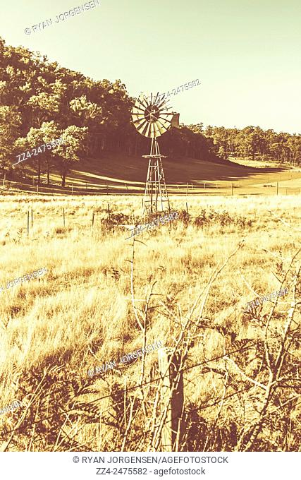 Rural farm ranch landscape with rustic windmill taken in vintage Australia countryside. Mathinna, Tasmania, Australia