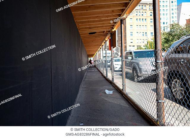 A covered walkway protects pedestrians traveling through an active building construction area, San Francisco, California, September 4, 2016