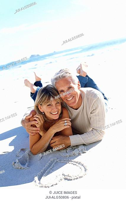 Mature couple lying on the beach, heart drawn in sand