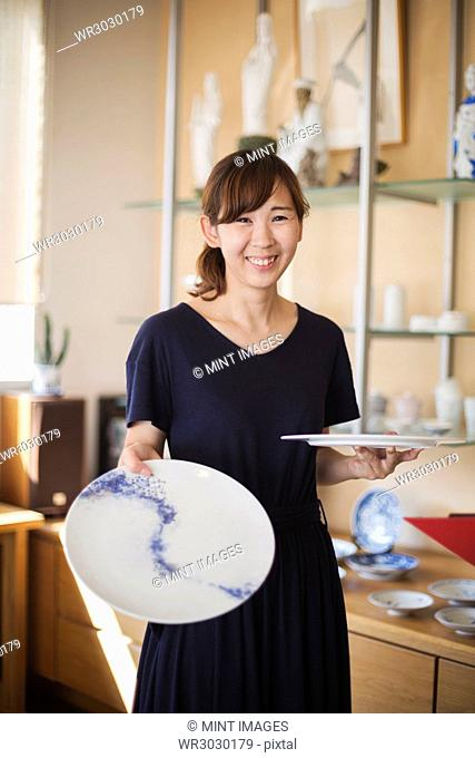 Smiling woman standing in a Japanese porcelain shop, holding two white plates with blue decoration