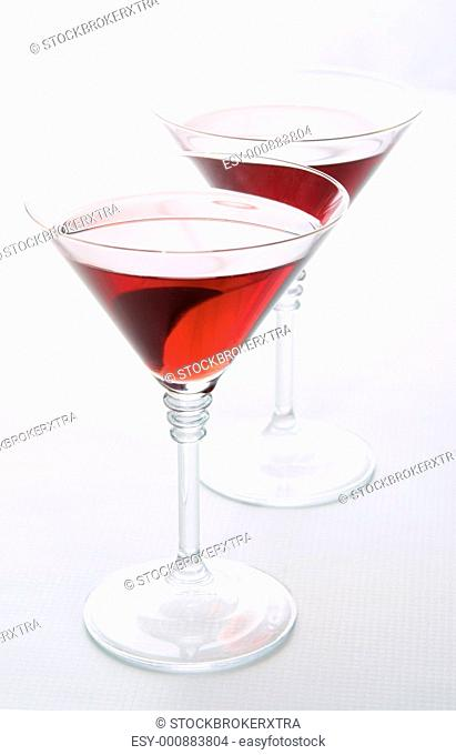 Two martini glasses with red wine over white background