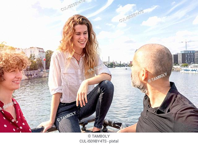 Man and female friends talking, river in background, Berlin, Germany