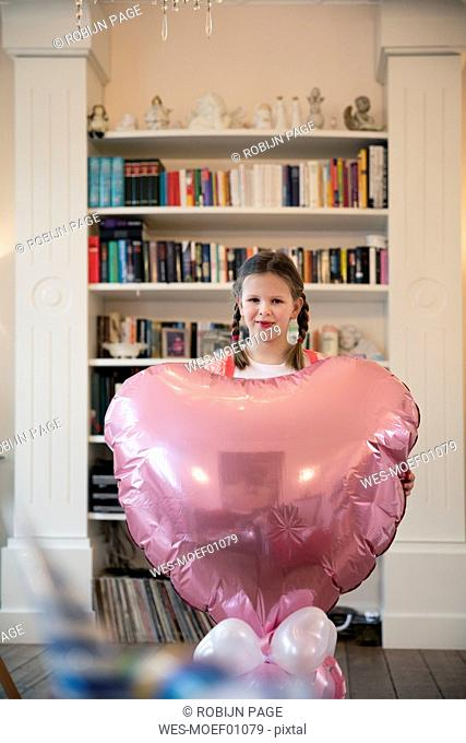 Portrait of girl with braids holding big heart-shaped balloon