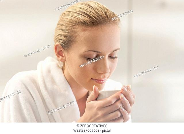 Young woman in bathrobe drinking tea