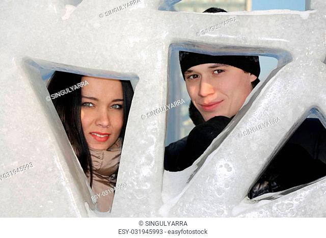 Boy and girl peep through triangular holes in big ice wall at winter day