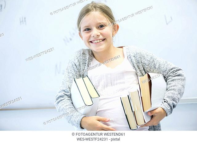 Portrait of happy schoolgirl carrying books in class