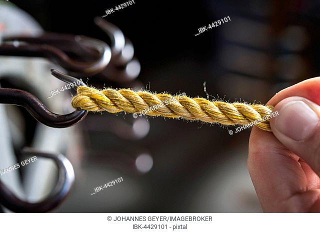 Passementerie maker, hand guiding cord on hook of cord twisting wheel, fifth work step to make twisted cord, Munich, Bavaria, Germany