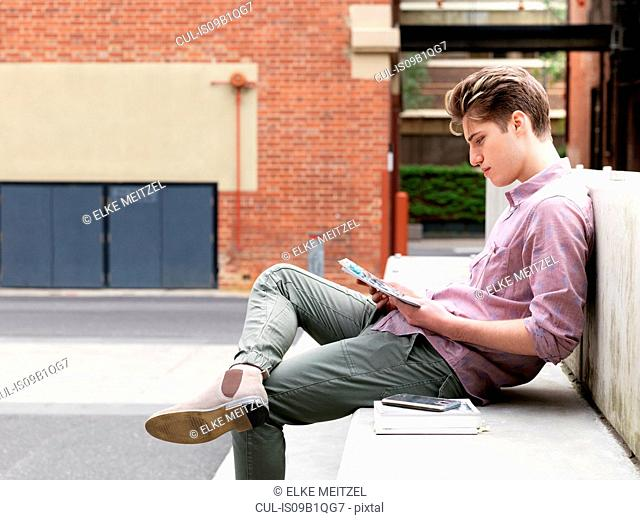 Young man sitting on step, outdoors, reading book