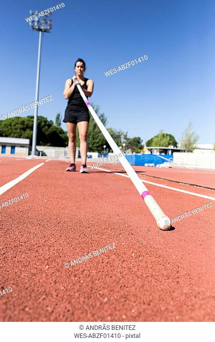 Female pole vaulter holding pole