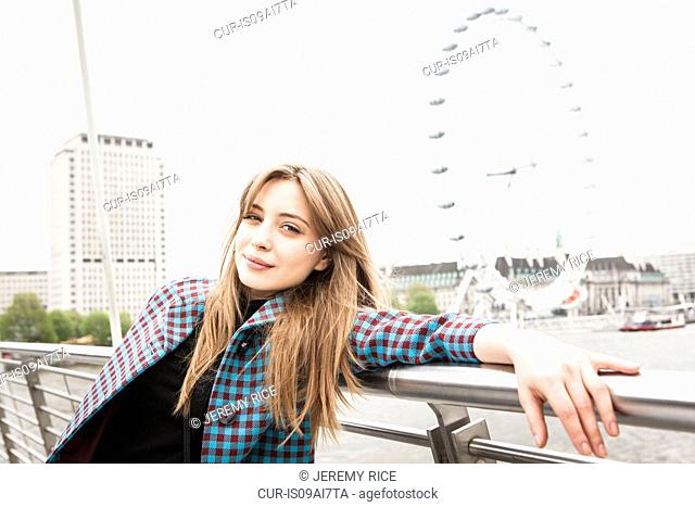 Portrait of young female tourist posing on Golden Jubilee footbridge, London, UK