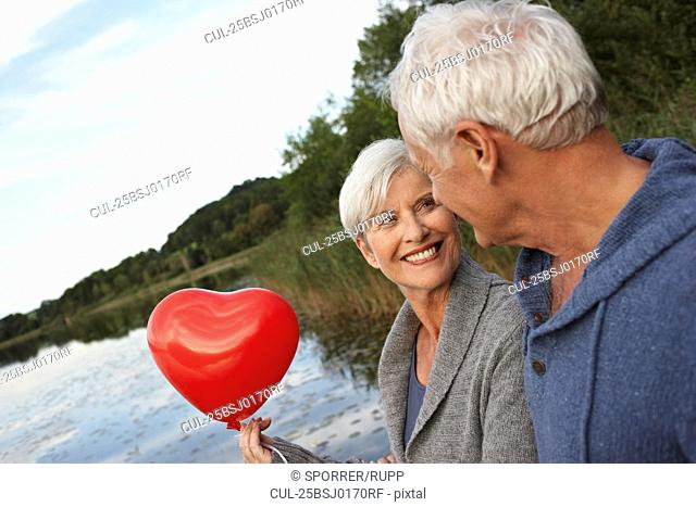 Senior couple holding red heart