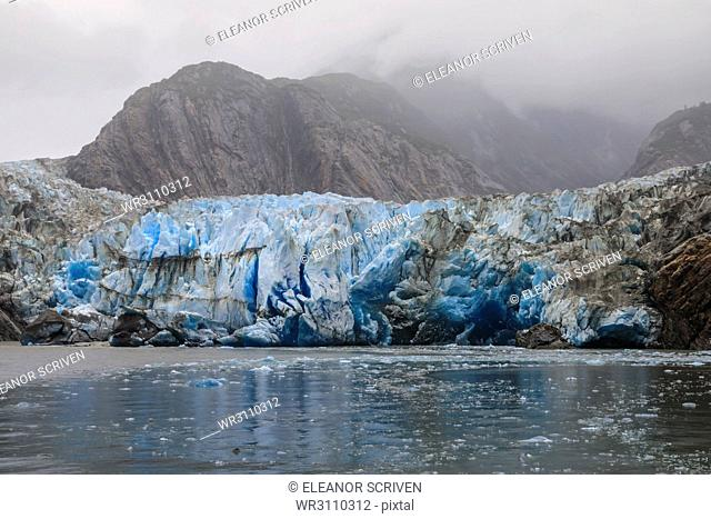 Blue ice face and floating ice, Sawyer Glacier and mountains, misty conditions, Stikine Icefield, Tracy Arm Fjord, Alaska, United States of America
