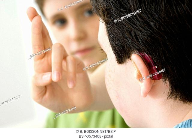 SIGN LANGUAGE Models. Do not use for HIV. A young boy and his brother using the French sign language to discuss with his hearing-impaired brother