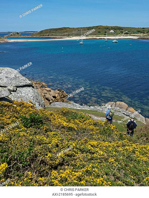 Hikers On The Coastal Path Around St Agnes With The Island Of Gugh And The Sand Bar In The Distance, Isles Of Scilly, Cornwall, Uk, Europe