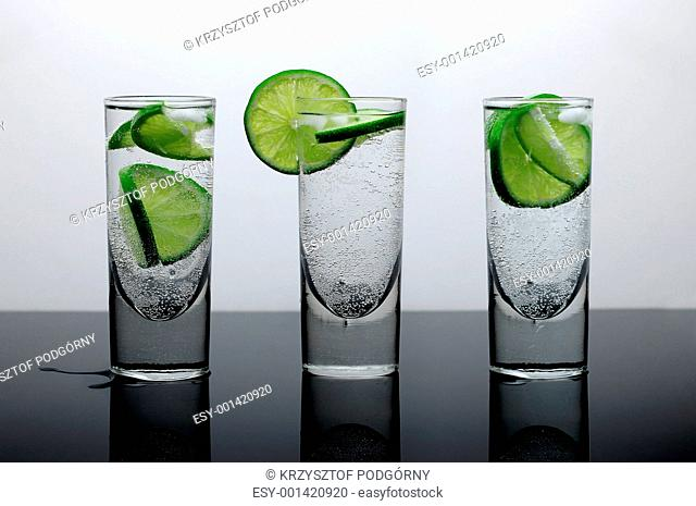 Fresh drink of water with lime and ice in three clear glasses