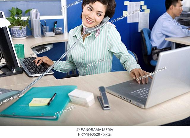 Young woman sitting at desk in office