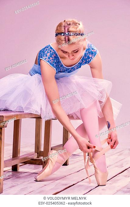 Professional ballerina putting on her ballet shoes on the wooden floor on a pink background
