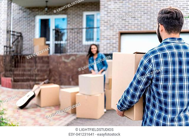 couple with cardboard boxes moving into new house