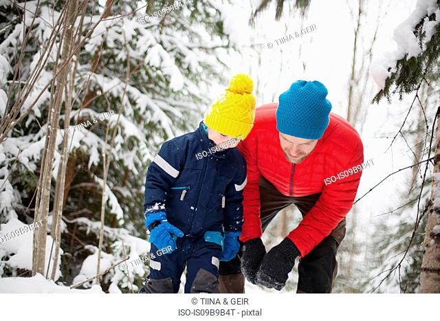 Man and son looking down in snow covered forest