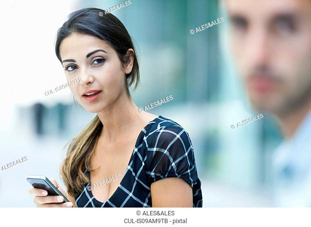 Woman using phone, colleague beside her