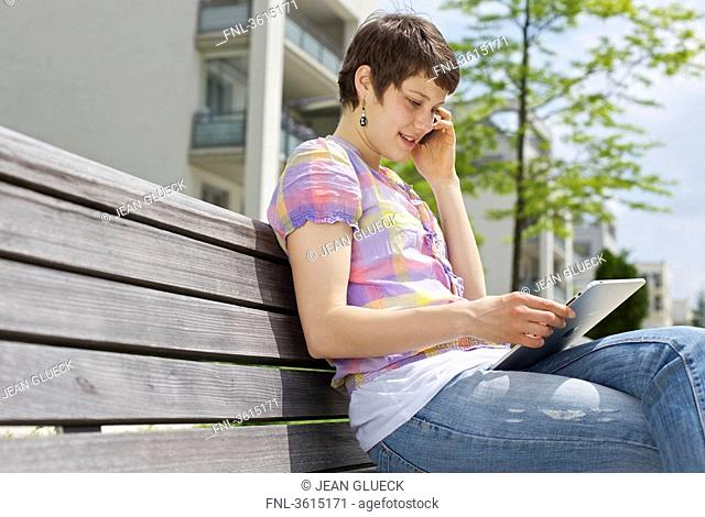 Young woman with cell phone and iPad on a bench