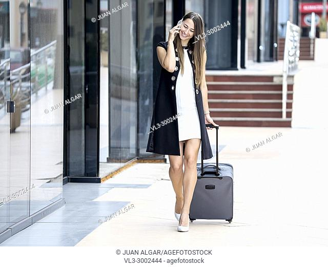Charming trendy woman in elegant outfit walking with suitcase at street and talking phone