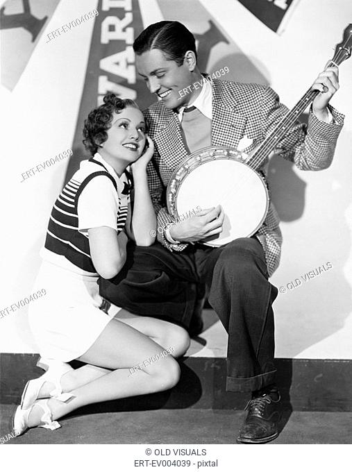 Man playing banjo for adoring woman All persons depicted are not longer living and no estate exists Supplier warranties that there will be no model release...