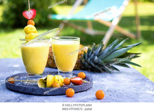 Two glasses of tropical smoothie with pineapple, mango, coconut milk and coconut flakes
