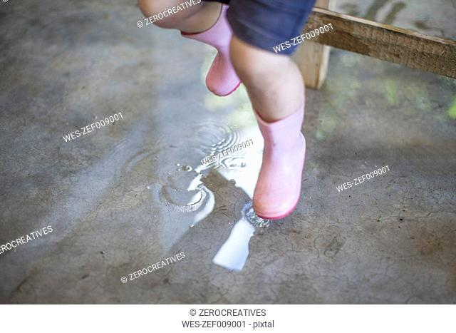 Little girl with pink gumboots jumping in puddle