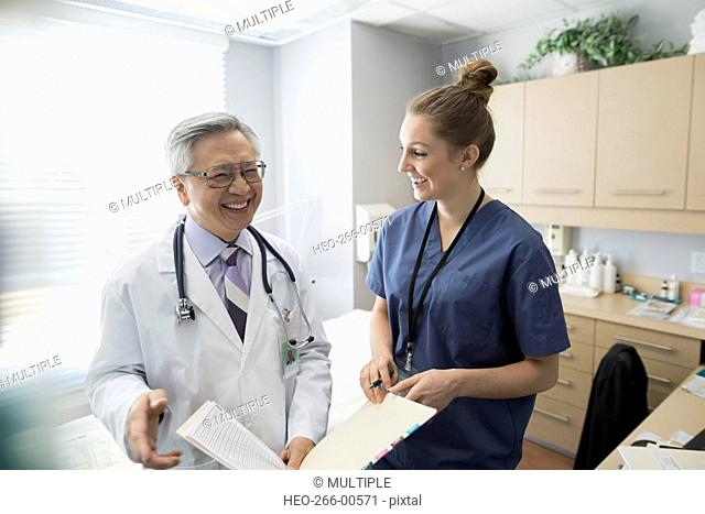 Laughing doctor and nurse reviewing medical record